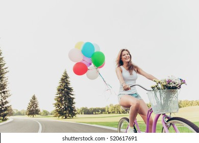happy girl riding on a bicycle with ballons and smiling