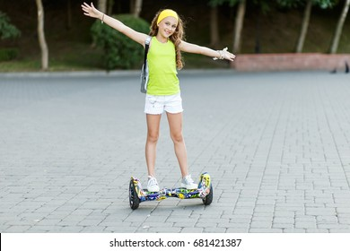 Happy girl  riding on hover board  or gyroscooter  outdoors at sunset in summer. Active life concept