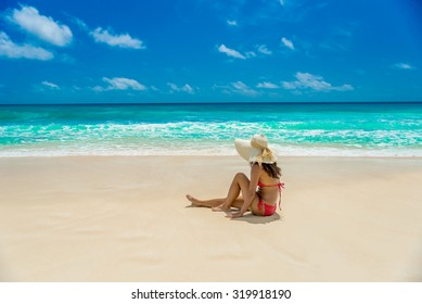 Happy girl running at beautiful beach on tropical island in Seychelles