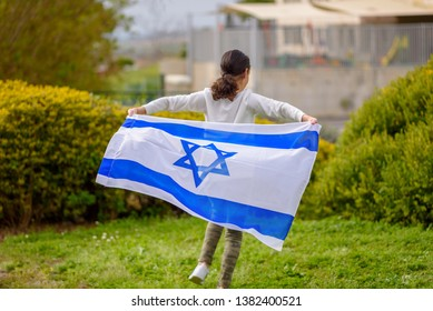 Happy Girl running with Israel flag. Image to illustrate election win, patriotic holiday Independence day Israel - Yom Ha'atzmaut concept.