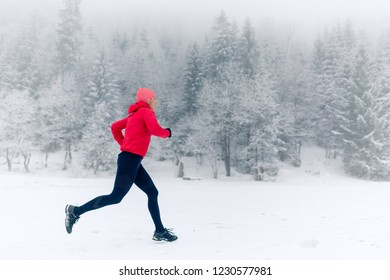 Happy girl running on snow in winter mountains. Sport, fitness inspiration and motivation. Young happy woman trail running in mountains on snow, winter day. Female trail runner jogging outdoors.