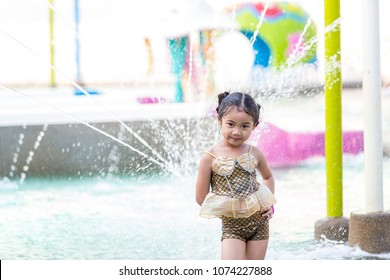 Happy girl is running through the fountain, enjoying the splash of water.