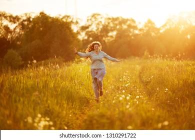 Happy girl running through the summer field