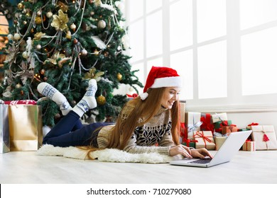 Happy girl in santa hat gereeting friends with christmas in video chat on laptop. Young woman lying under decorated pine tree among gift boxes and packages in home interior with copy space on window