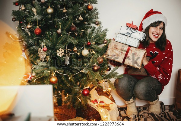 happy girl in santa hat holding many gift boxes at golden beautiful christmas tree with lights in festive room. happy winter holiday atmospheric moments. seasons greetings. Merry Christmas