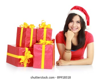 Happy girl in santa hat with pile of xmas gifts  isolated on white background
