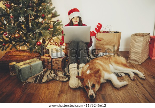happy girl in santa hat shopping online on laptop and sitting with cute dog at golden beautiful christmas tree with lights and presents in festive room. christmas sale and discount concept