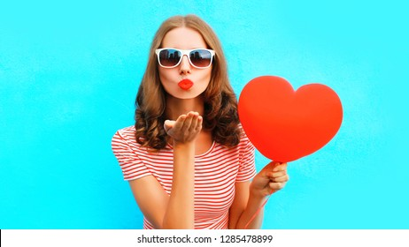 Happy girl sends air kiss with red balloon heart shape over blue background