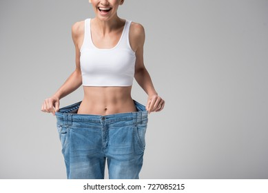 Happy girl showing her slim figure after workout