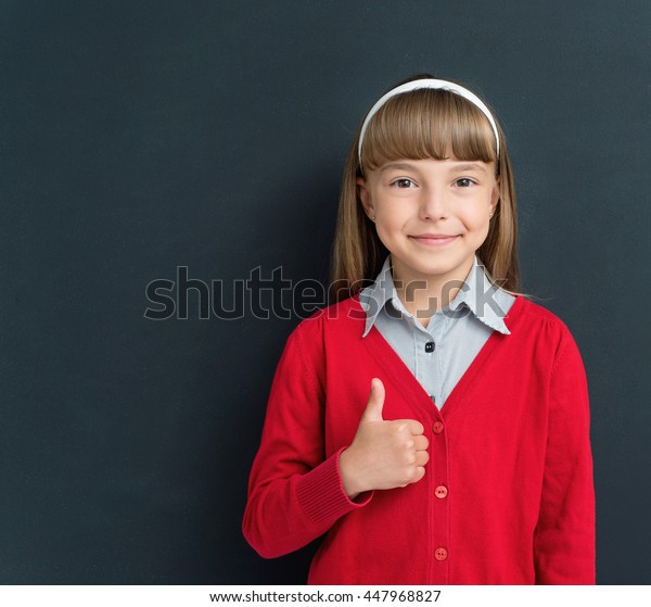 Happy girl showing thumb up gesture in front of a big chalkboard. Back to school concept.