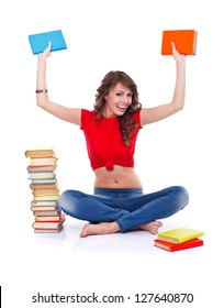 Happy girl sitting in the floor holding colorful books in hand