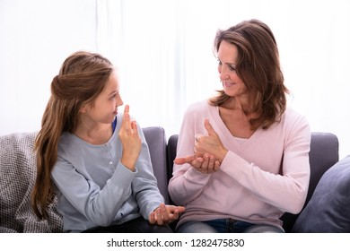 Happy Girl Sitting On Sofa Learning Sign Languages From Woman