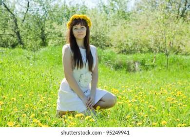 Happy girl sitting outdoor in dandelion wreath