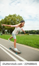Happy girl skating on a longboard, natural background