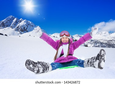 Happy girl sliding on sled with her hands lifted, wearing ski mask, in the mountains