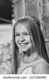 Happy girl. small girl kid with long blonde hair and pretty smiling happy face in dress and prom princess crown standing on sunny background, closeup