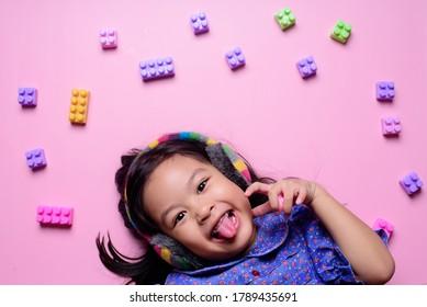 happy girl smile  with toy indoor studio light pink background