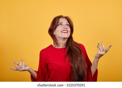 Happy girl smiling, holding both hands at the chest level, looking upwards. Young woman in red wearing apparel stands on orange back burner.