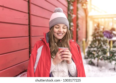 Happy girl smiling holding cup of coffee or tea. In red jacket on background of wooden shutters on street. Warms about a cup with a hot drink. Woman resting at an event in winter in city.