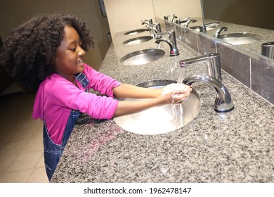 Happy girl smiling while washing hands in public restroom