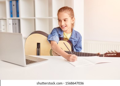 Happy girl smiling and writing in notebook while watching online course on laptop and learning to play guitar at home