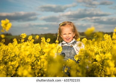 Happy girl smiling in yellow blossoming rapeseed field