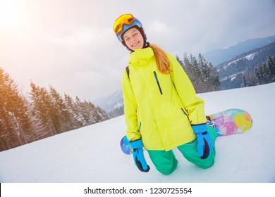 Happy girl snowboarder enjoys the winter ski resort.