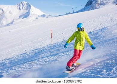 Happy girl snowboarder having fun in the winter ski resort.