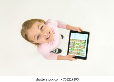 The happy girl stand with a tablet. View from above