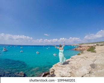 Happy girl standing on the cliff with the gorgeous turquoise sea view, Ibiza, Balearic islands