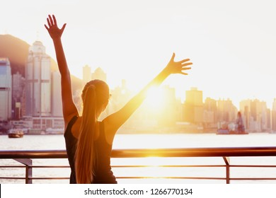 Happy girl stands with raised hands against sunset and looking at Hong Kong city