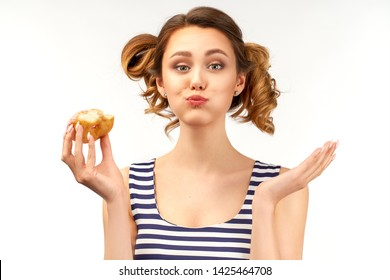 A happy girl in a striped t-shirt holds a donut in her hand and chews a donut with her mouth full. Funny cute expression of a young sweet tooth. The concept of a quick and tasty snack.