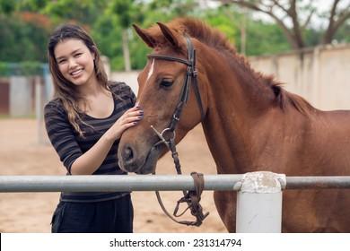 Happy girl stroking bay pony at the ranch