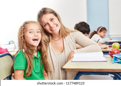 Happy girl as a student with tutoring teacher in elementary school