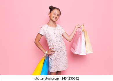 Happy girl in a stylish dress, a teenager with purchases in her hands, after a shopping trip, points to an empty space on a pink background