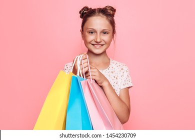 Happy girl in stylish dress, teenager with purchases in hand, after a shopping trip on a pink background