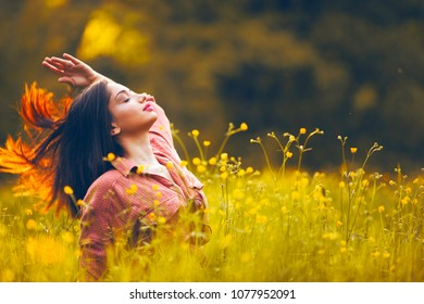 Happy girl in the summer. Free young woman flipping hair over flower field. Happiness, Freedom and Break-up Concept