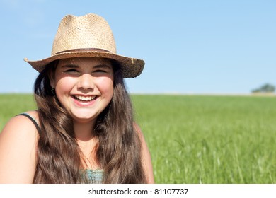 Happy girl with sun hat. Outdoor shot against a blue sky on a fresh green lawn.
