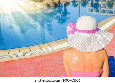 happy girl with the sun on her back at the pool in the nature