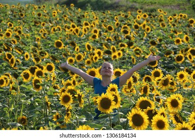 Happy girl in sunflower field