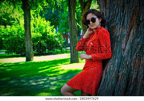 Happy girl in sunglasses dressed in red summer dress posing leaning park tree in summertime, copyspace