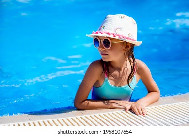 Happy girl in Sunglasses and hat in outdoor swimming pool of luxury resort on summer vacation. Healthy outdoor sport activity for children. Kids beach fun