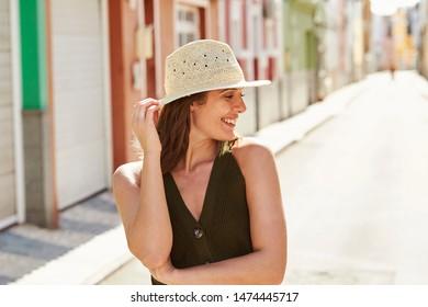 Happy girl in sunhat, smiling in street