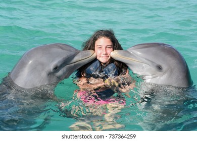 happy girl swimming with dolphins
