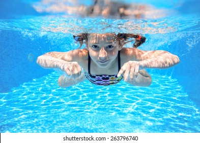 Happy girl swims in pool underwater, active kid swimming, playing and having fun, children water sport