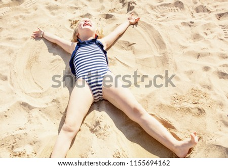happy girl in swimsuit laying on sand and making angel on the seashore