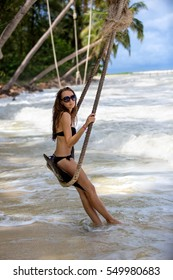 Happy girl swinging on a swing on a palm tree in Thailand. Holidays in Asia on the beach