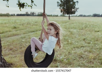 Happy girl swinging on a wheel, walk in nature