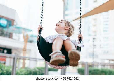 Happy girl swinging outdoors on the playground