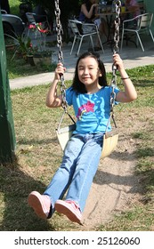 Happy girl swinging at the playground in the park on sunny day